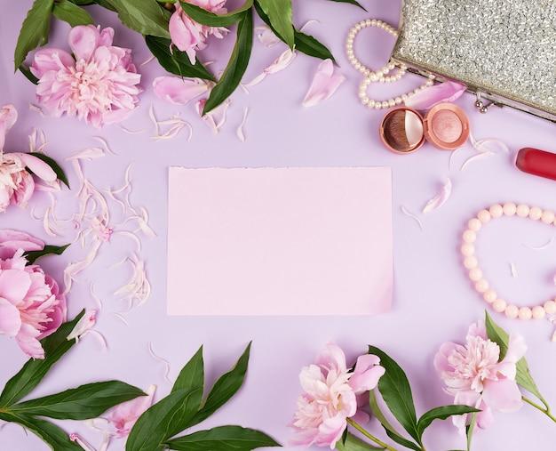 Page rose, bouquet de pivoines, rouge à lèvres et une pochette argentée