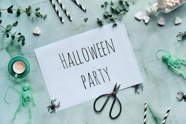 Page avec texte halloween party. mise à plat monochrome avec eucalyptus, bougie chauffe-plat, ciseaux, yeux écarquillés, squelettes, araignées