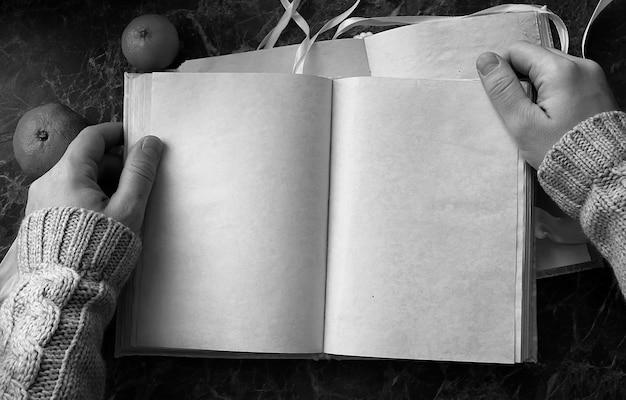 Pages blanches ont ouvert un livre vintage sur un comptoir en marbre vert