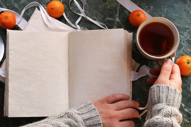 Des pages blanches ont ouvert un livre vintage sur un comptoir en marbre vert