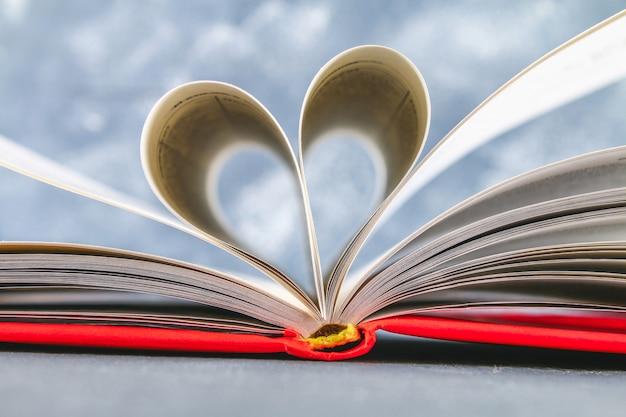 Les pages du livre à la couverture rouge sont en forme de cœur. le concept saint valentin.