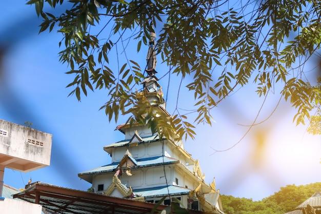 La pagode de l'architecture birmane avec des feuilles vertes couvrant le front pendant la journée.
