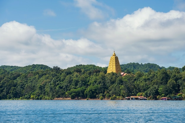 Pagode d'or de bodhgaya et village local de maisons de radeau avec forêt d'arbres contre le ciel bleu et les nuages à sangkhlaburi, kanchanaburi, thaïlande. célèbre destination de voyage capturée en bateau depuis la rivière.