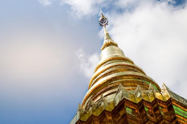 La pagode d'or est allumée dans le temple avec le soleil qui brille à travers.