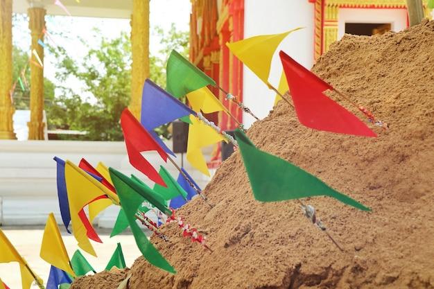 Pagode de sable du festival songkran, thaïlande, avec des drapeaux en papier coloré sur le tas de sable.