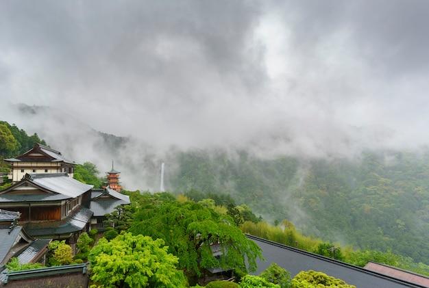 Pagode sanjudo à trois étages du temple seiganto-ji avec les chutes de nachi et de beaux paysages brumeux en arrière-plan, classée au patrimoine mondial de l'unesco dans la préfecture de wakayama, japon