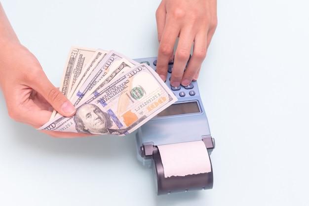 Paiement des achats en espèces, en dollars. gros plan d'une main donnant de l'argent et main tapant le montant, comptant à la caisse enregistreuse sur fond bleu. concept d'entreprise, concept de vendredi noir