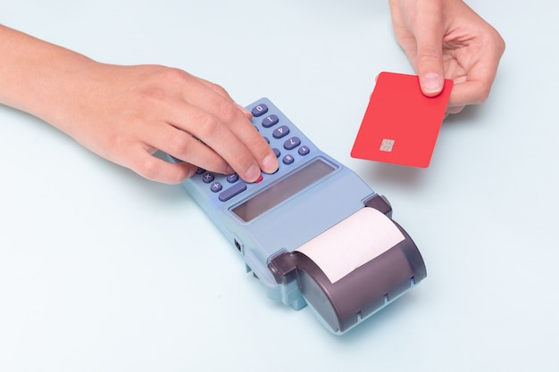 Paiement des achats par carte de crédit. gros plan sur une main tenant une carte bancaire et une main tenant un chèque, reçu sur une caisse enregistreuse sur fond bleu, vente au détail, vente en ligne. concept de vendredi noir