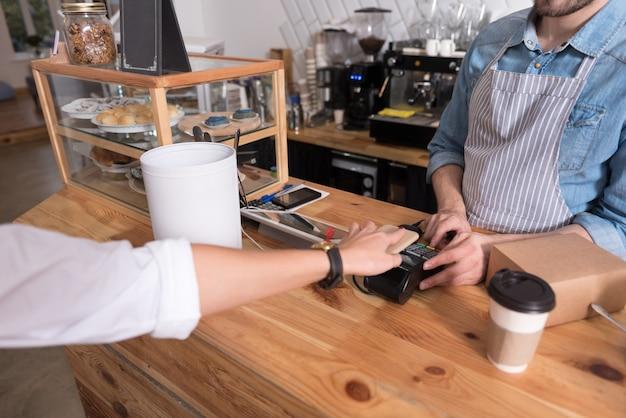 Paiement confortable. gros plan de la main de la femme à l'aide du terminal tandis que le jeune serveur debout derrière le bar et travaillant