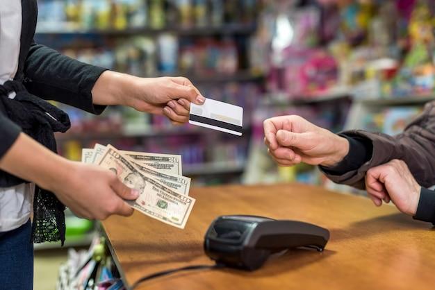 Paiement dans un magasin de jouets avec des dollars et une carte de crédit