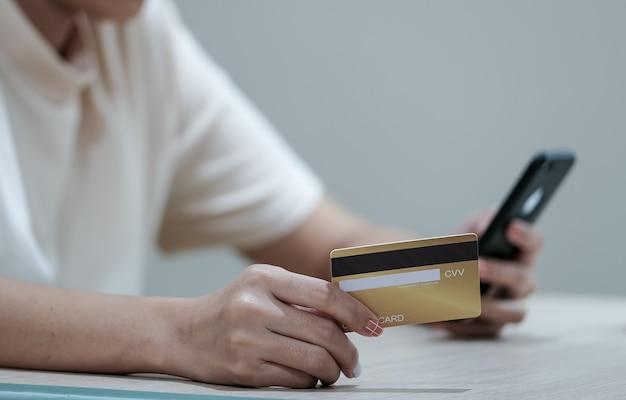 Paiement en ligne et achats, mains de femme tenant une carte de crédit et à l'aide d'un smartphone