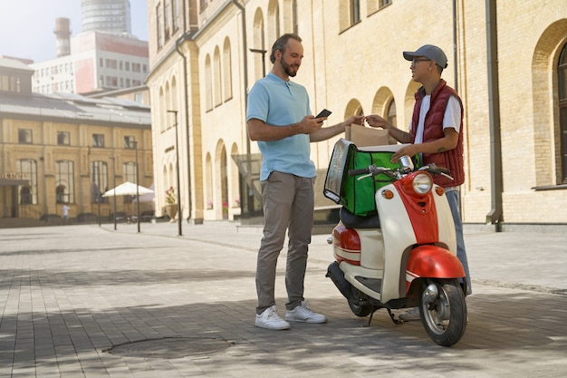 Paiement en ligne jeune homme gai recevant un sac en papier avec de la nourriture