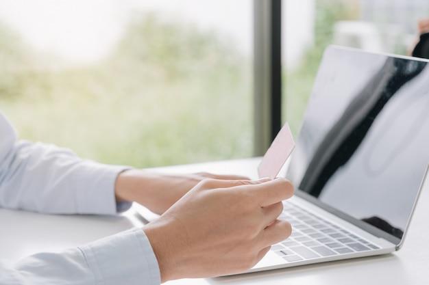 Paiement en ligne, mains de femme tenant une carte de crédit et utilisant un ordinateur portable pour faire des achats en ligne