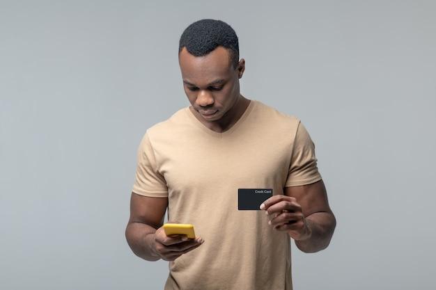 Paiement mobile. homme noir attentif sérieux avec carte de crédit à la recherche de smartphone en transaction de paiement
