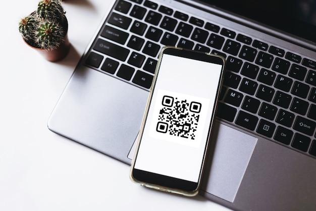 Paiement par balayage de code qr et concept d'achat en ligne téléphone mobile sur l'ordinateur portable