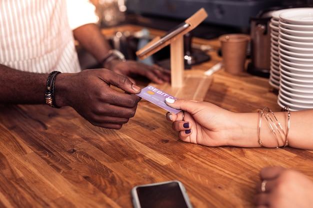 Paiement par carte. bel homme afro-américain prenant une carte de débit tout en faisant une transaction d'argent