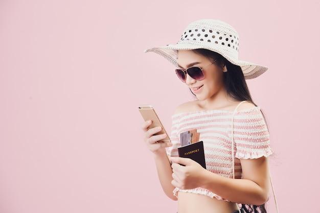 Paiement pour les achats en ligne., femme joyeuse appréciant les achats en ligne par smartphone et carte de crédit sur fond rose studio. filtres de tons rose pastel.