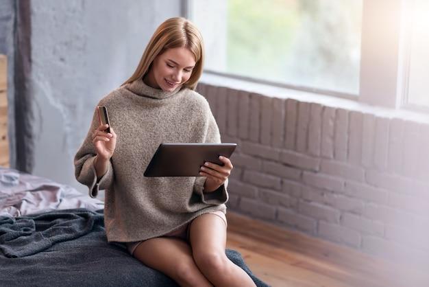 Paiement réussi. jolie jeune femme ravie à l'aide de carte de crédit et tablette tout en souriant et assis dans son lit.