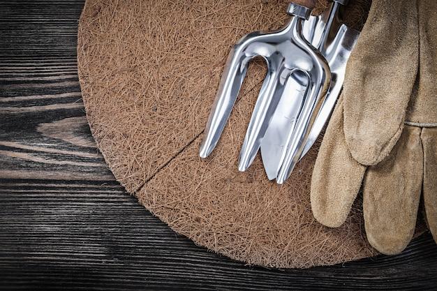 Paillage cercle pelle truelle fourche gants de protection en cuir sur planche de bois