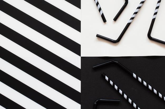 Pailles de cocktail rayées sur fond noir et blanc dans un style minimal