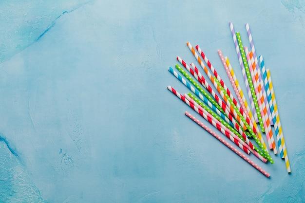 Pailles colorées en papier à boire pour les cocktails d'été sur bleu clair