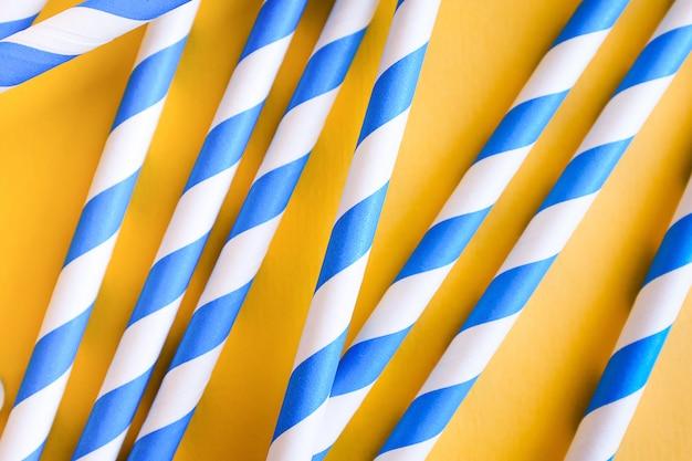 Pailles colorées, réutilisables, à rayures, pour boire du jus ou un cocktail sur fond jaune.