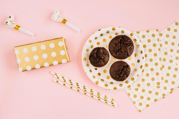 Pailles et cornes de fête près du cadeau et du dessert