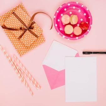 Pailles et feuille de papier près du cadeau et des macarons