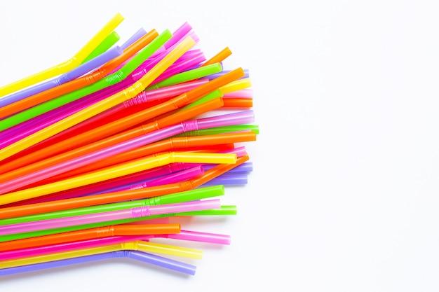 Pailles en plastique colorées sur blanc