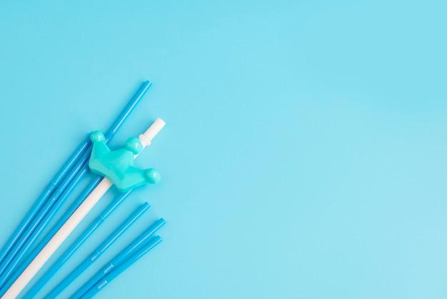 Pailles en plastique sur fond bleu, espace copie