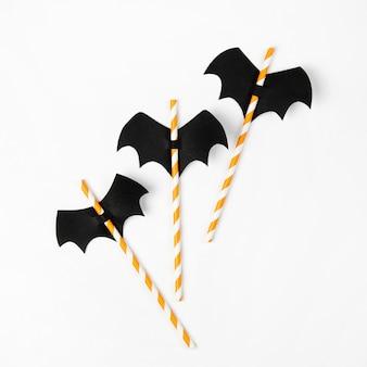 Pailles rayées avec des chauves-souris en papier sur fond blanc. décorations de vacances d'halloween. mise à plat, vue de dessus