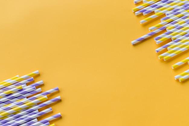 Pailles à rayures de différentes couleurs en rangée isolé sur fond jaune
