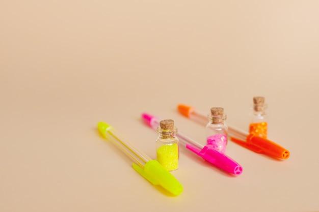 Paillettes colorées dans des bouteilles et stylos lumineux pour l'écriture