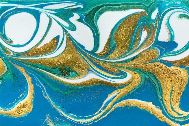 Paillettes et éclats de lumière doré d'un liquide bleu et vert irrégulier