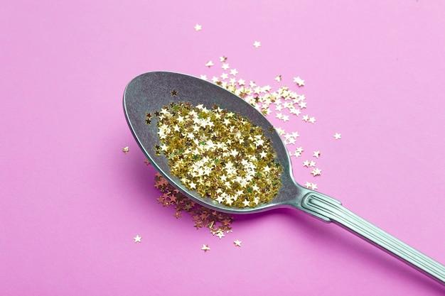 Paillettes d'or dans une cuillère sur une surface rose
