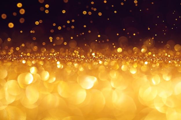 Paillettes d'or de noël avec des étincelles. coup de macro, fond abstrait