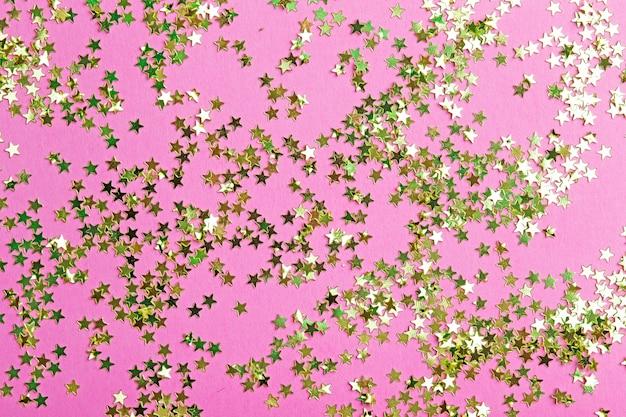 Paillettes d'or sur une surface rose