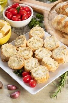 Pain à l'ail dans une assiette carrée blanche sur la table avec du fromage, du romarin, des olives et des tomates cerises. vue de dessus.