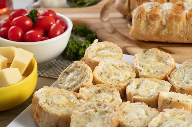 Pain à l'ail dans une assiette carrée blanche sur la table avec du fromage, du romarin, des olives et des tomates cerises.