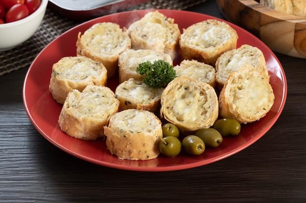 Pain à l'ail sur une plaque rouge sur la table du barbecue avec saucisse, fromage, romarin, olives et tomates cerises.