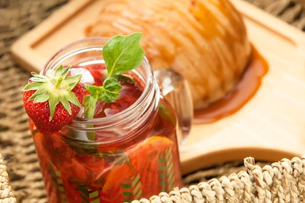 Pain arrosé de miel sur une assiette en bois et un verre avec un cocktail dans un panier en osier