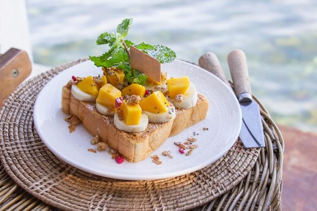 Pain au beurre d'arachide dans une assiette blanche avec fond de mer.