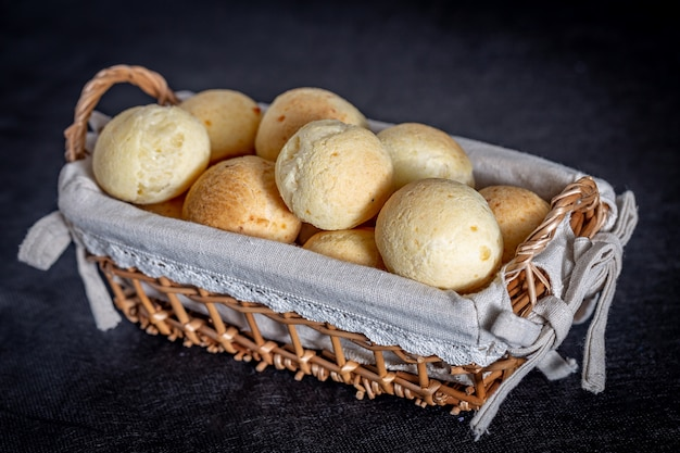 Pain au fromage brésilien fait maison, aka 'pao de queijo' dans un panier rustique.