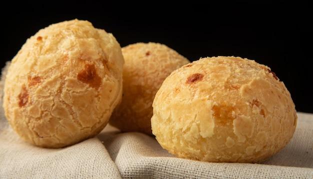 Pain au fromage du brésil, arrangement avec du pain au fromage sur tissu sur fond noir