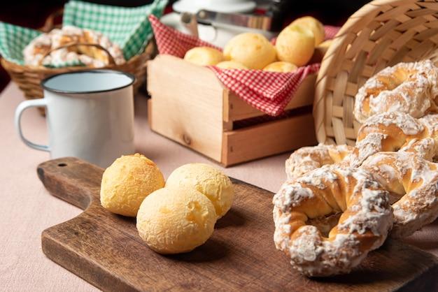 Pain au fromage du brésil et biscuit sucré et une tasse de café sur une table avec nappe beige, mise au point sélective.