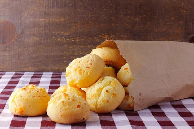 Pain au fromage fait maison, collation brésilienne traditionnelle, dans un sac en papier rustique sur une table de cuisine