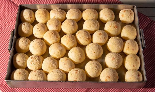 Pain au fromage, forme remplie de pain au fromage qui vient de sortir du four sur une nappe à carreaux, vue de dessus.