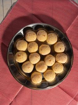 Pain au fromage, forme ronde garnie de pain au fromage qui vient de sortir du four sur une nappe à carreaux, vue du dessus.