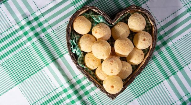 Pain au fromage, panier en forme de coeur garni de tissu vert et blanc rempli de pain au fromage sur une nappe à carreaux, vue du dessus.