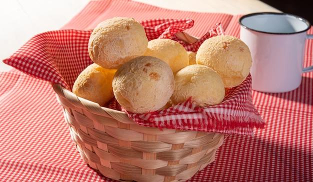 Pain au fromage, panier garni de tissu rouge et blanc rempli de pain au fromage sur une serviette à carreaux et une tasse blanche.